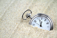 Pocket watch semi buried in the sand Stock Images