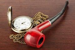 Pocket watch and smoking tube Stock Photos