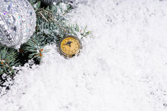 Pocket Watch in Snow Beside Decorated Evergreen Stock Image