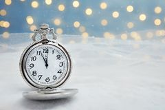 Pocket watch with snow on table against blurred lights. Christmas countdown. Open pocket watch with snow on table against blurred lights. Christmas countdown stock photo