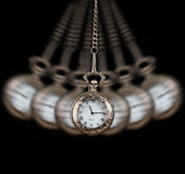 Pocket watch swinging on a chain black background stock images