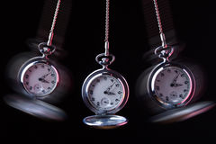 Pocket watch swinging on a chain to hypnotise. Black background Royalty Free Stock Photos