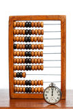 Pocket watch on table against wooden abacus Stock Image