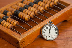 Pocket watch on table andt wooden abacus Stock Photos