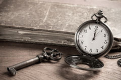 Pocket watch. Vintage Key, Book and Pocket Watch. The Key is in Time Stock Photo
