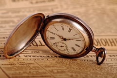 Pocket watch on vintage newspaper Stock Images