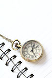 Pocket watch on white notebook page Stock Photo