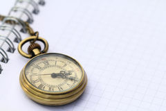 Pocket watch on white notebook page Stock Photos