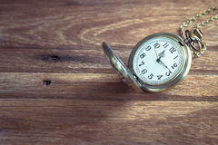 Pocket watch on wooden background Royalty Free Stock Photo