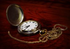 Pocket watch on wooden background. Pocket watch with chain on red wooden background stock images