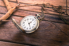 Pocket watch on wooden background, vintage style light Royalty Free Stock Image
