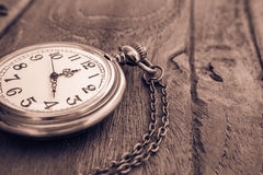 Pocket watch on wooden surface, vintage style Stock Image