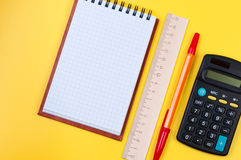 Pocketbook and calculator on yellow background. Stock Photo