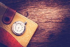 Pocketbook and old pocket watch on wooden background. Royalty Free Stock Photo