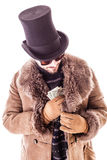 Pocketing dollars. A young man wearing a sheepskin coat and a top hat isolated over a white background holding banknotes Royalty Free Stock Images