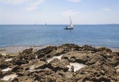 Pockets of sea salt in limestone rocks, sailboats on Palma bay. Royalty Free Stock Images