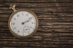 在概略的木背景的老Pocketwatch 免版税图库摄影