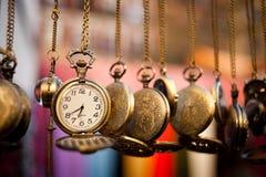Pocketwatches, das über Mehrfarbenhintergrund hängt Stockbild