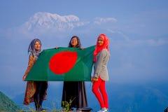 Pockhara,尼泊尔, 9月, 06 -2017 :关闭佩带hijab和拿着旗子的三名美丽的尼泊尔妇女  免版税库存照片