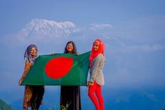 Pockhara,尼泊尔, 9月, 06 -2017 :关闭佩带hijab和拿着旗子的三名美丽的尼泊尔妇女  免版税库存图片