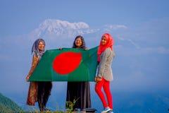 Pockhara, Népal, septembre, 06 -2017 : Fermez-vous de trois belles femmes népalaises portant un hijab et tenant un drapeau dedans Photographie stock