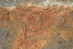 POCKMARKED TEXTURE OF ROCK SURFACE. View of the surface of a red rock with small indentations and holes Royalty Free Stock Photography