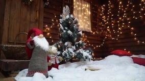Poco árbol de navidad en la nieve cerca de una casa adornada con las guirnaldas paralaje almacen de metraje de vídeo