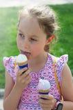 Poco 7 años de la muchacha del helado de Eatting, fondo verde del parque de Blured Adultos jovenes fotografía de archivo libre de regalías