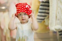Poco 3 años lindos de muchacha en un lunar rojo del sombrero en la tienda de la ropa de los niños Fotos de archivo libres de regalías