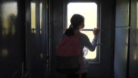 Poco adolescente es un backpacker que viaja en tren concepto del ferrocarril del transporte del viaje colegiala turística adentro almacen de video