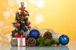 Poco adornó maravillosamente el árbol de navidad, regalos, conos, juguete-globos, en fondo amarillo Imagen de archivo libre de regalías