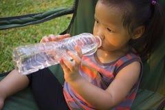 Poco agua potable de los ni?os de la botella en parque verde fotografía de archivo