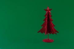 Poco albero di Natale rosso su fondo verde Fotografie Stock