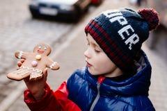 Poco 7 anni del ragazzo che mangia l'uomo di pan di zenzero Immagine Stock Libera da Diritti