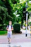 Poco 7 anni dello scolaro di strada dell'incrocio su luce verde fotografia stock