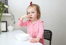 Poco 2 anni di ragazza che mangia a casa cucina Fotografia Stock