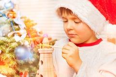 Poco ayudante del ` s de Papá Noel que adorna el juguete con la pintura foto de archivo