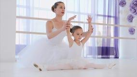 Poco bailarina en el tutú blanco está estirando en la lección del ballet con el profesor metrajes