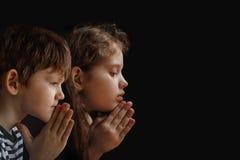Poco bambino ha piegato la sua mano con pregare nel fondo nero fotografie stock libere da diritti