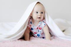 Poco bambino smirking sotto il tappeto del biege fotografie stock