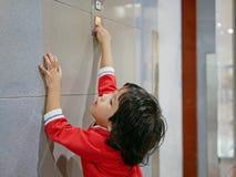 Poco bebé asiático, 3 años, alcanzándola para distribuir para intentar empujar el botón del elevador imágenes de archivo libres de regalías