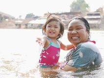 Poco bebé asiático goza el jugar del agua en un río con su tía foto de archivo libre de regalías