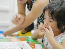 Poco bebé asiático que aprende escribir números en casa imágenes de archivo libres de regalías