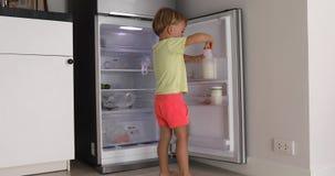 Poco bebé con el refrigerador de la leche de la botella de la tapa almacen de video