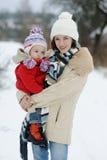 Poco bebé del invierno y su madre joven foto de archivo libre de regalías