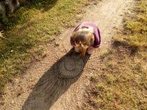 Poco bebé dibuja el sol en el medio de un camino arenoso del pueblo imagenes de archivo