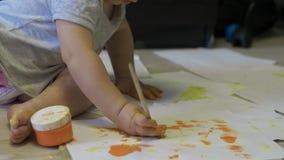 Poco bebé dibuja las pinturas en el papel en la cámara lenta metrajes