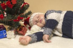 Poco bebé en el sombrero de Papá Noel que duerme debajo del árbol de navidad imagen de archivo libre de regalías