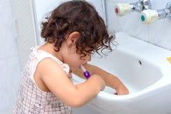 Poco bebé lindo que limpia sus dientes con el cepillo de dientes en el cuarto de baño foto de archivo
