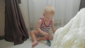 Poco bebé que juega con los pequeños bloques coloridos de un constructor en el cuarto en el piso Niño que juega con coloreado almacen de metraje de vídeo